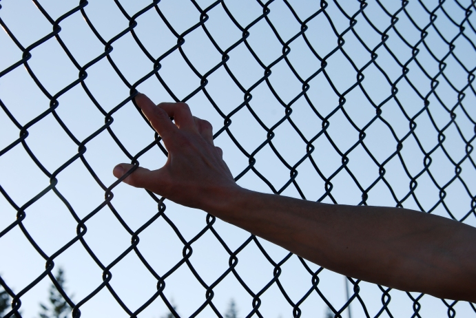 Leaning against a chain link fence during a sport